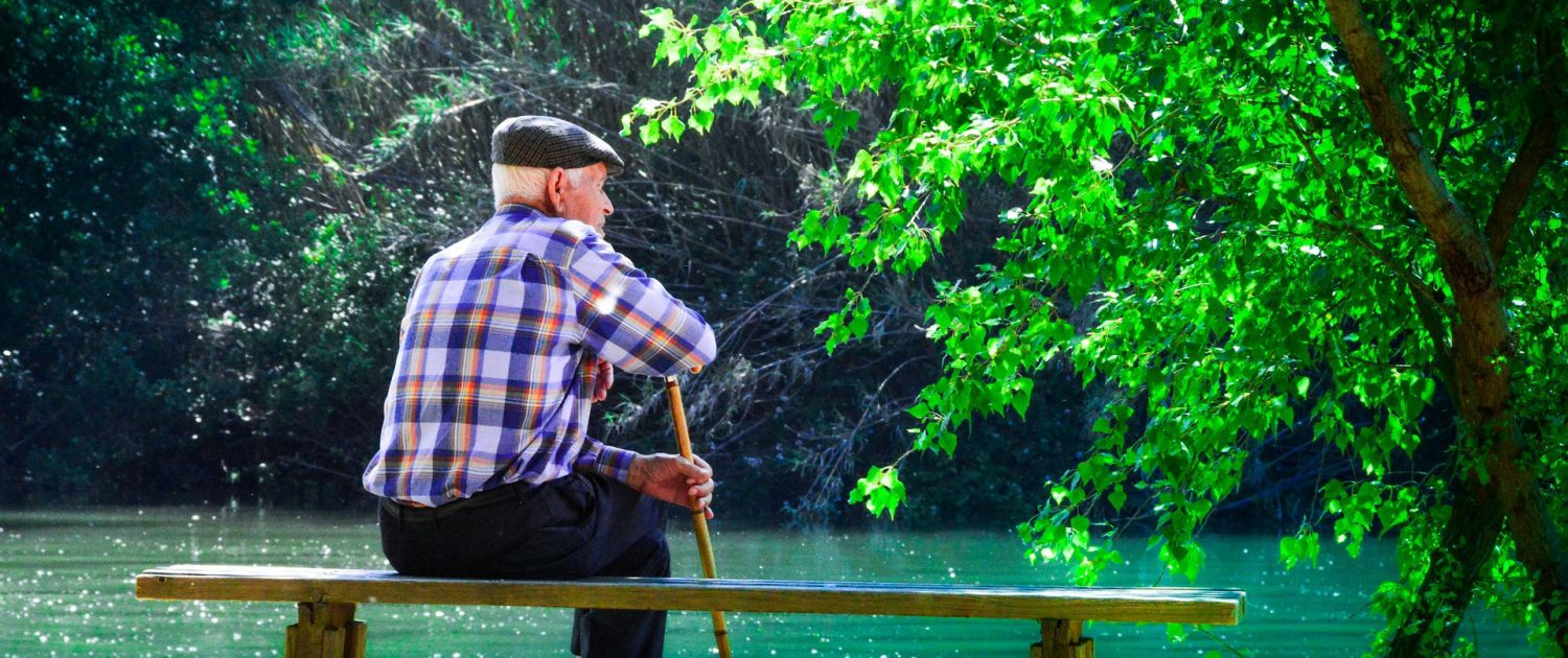 Elder sitting on waters edge